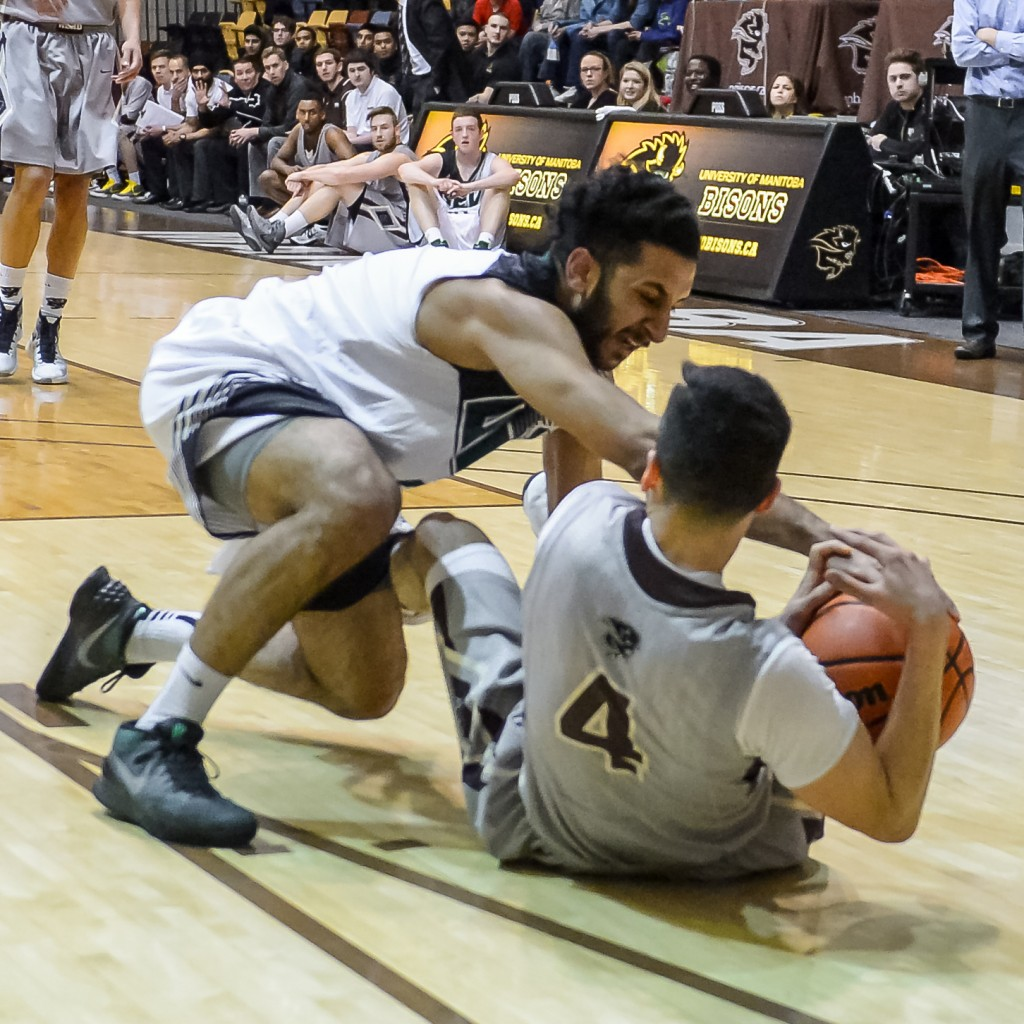 UFV's Vijay Dhillon battles for a loose ball with Manitoba's AJ Basi. (Jeff Miller / Bison Sports)