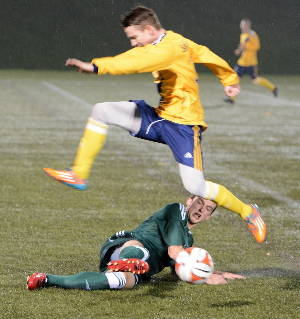 Daniel Davidson of the Cascades slides to knock the ball away from a TWU Spartans opponent.