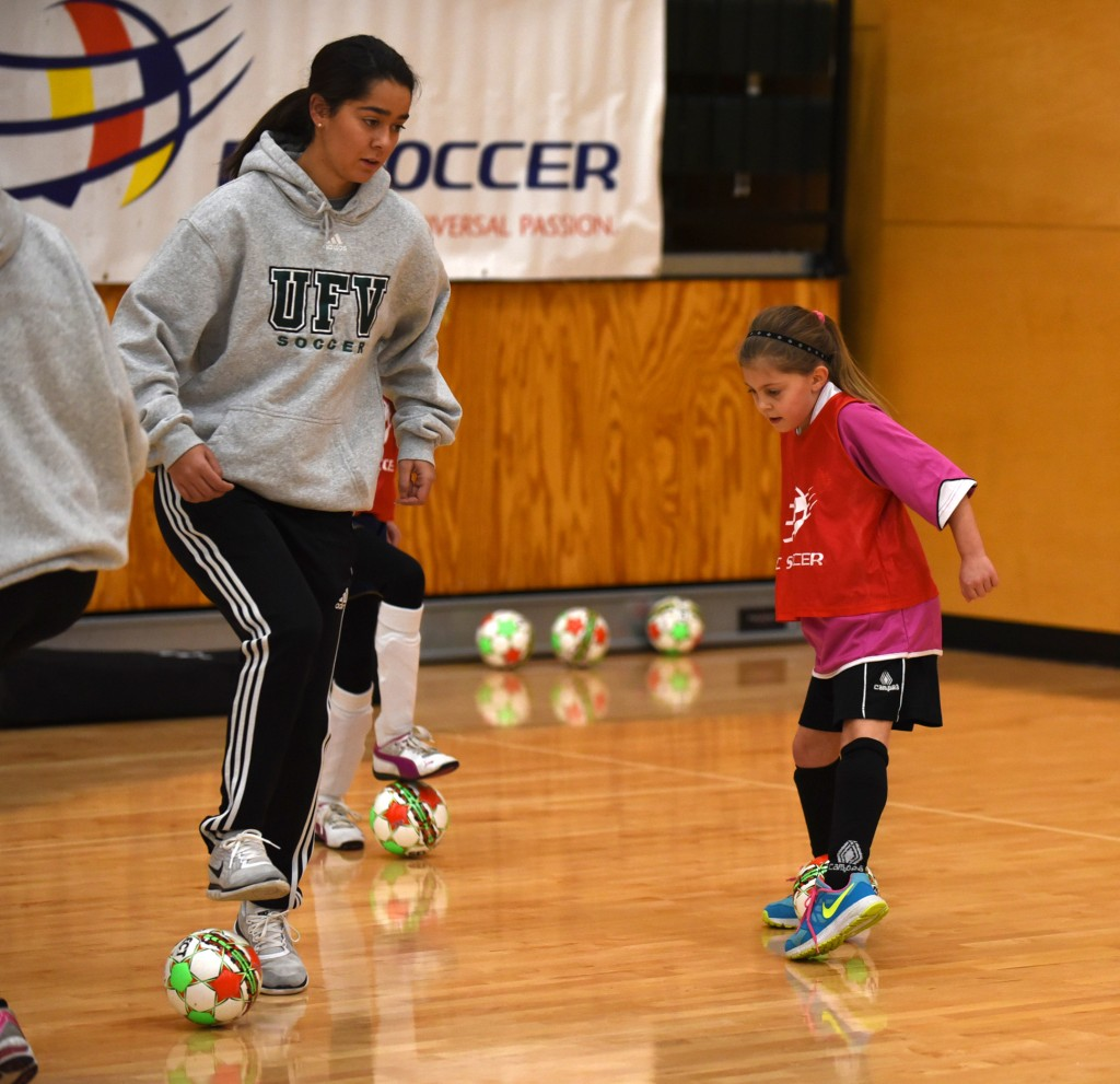 Lexi Gillette, an incoming player with the Cascades women's soccer team, works on skills with a young player during last week's futsal festival at UFV. (Peter Lonergan photo / BC Soccer)
