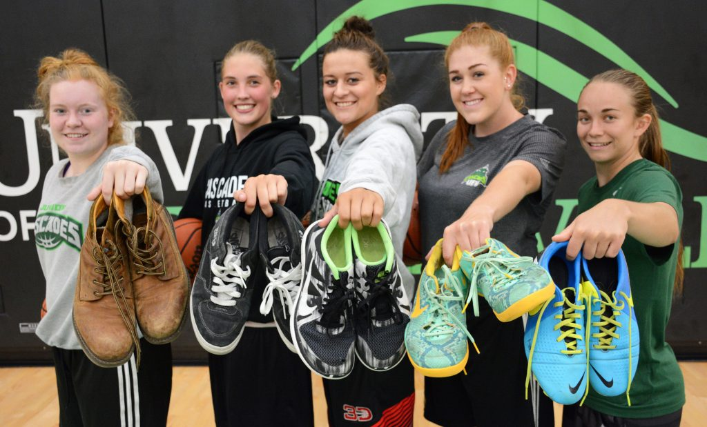Katherine Holden, Jessica Cameron, Amanda Thompson, Taylor Claggett and Amelia Worrell of the Cascades hold up some of the shoes they've collected for Soles4Souls.