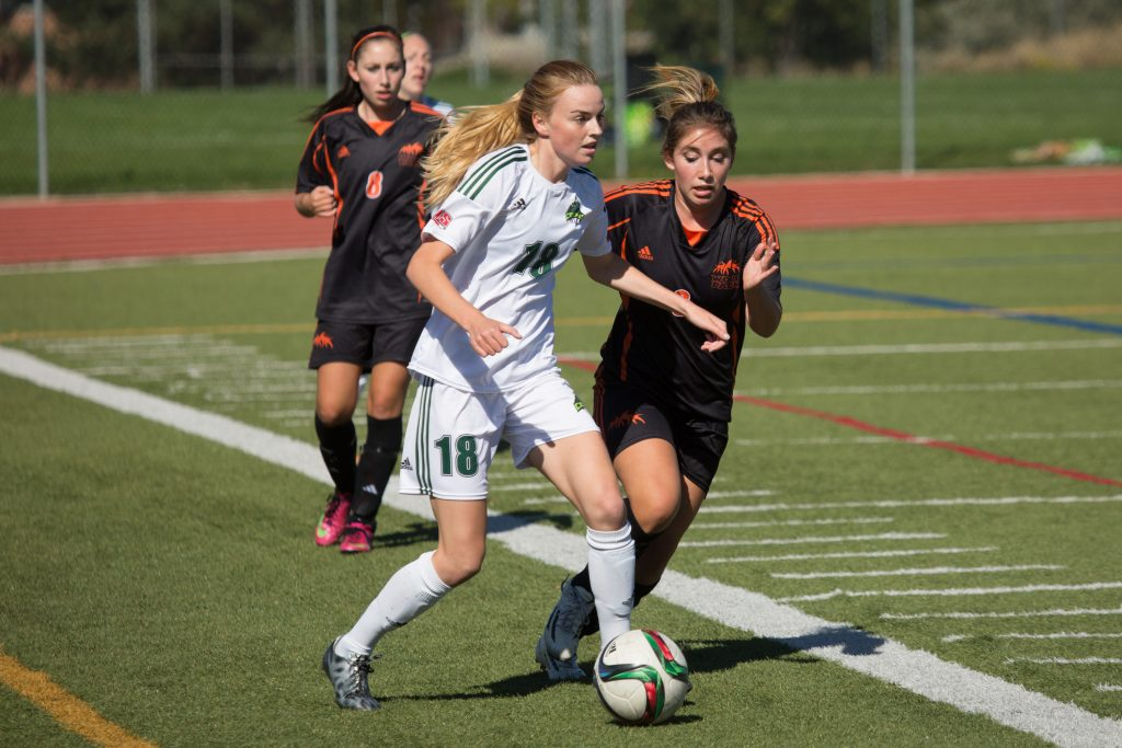 UFV's Amanda Carruthers pushes the ball up the pitch with a TRU defender in pursuit.