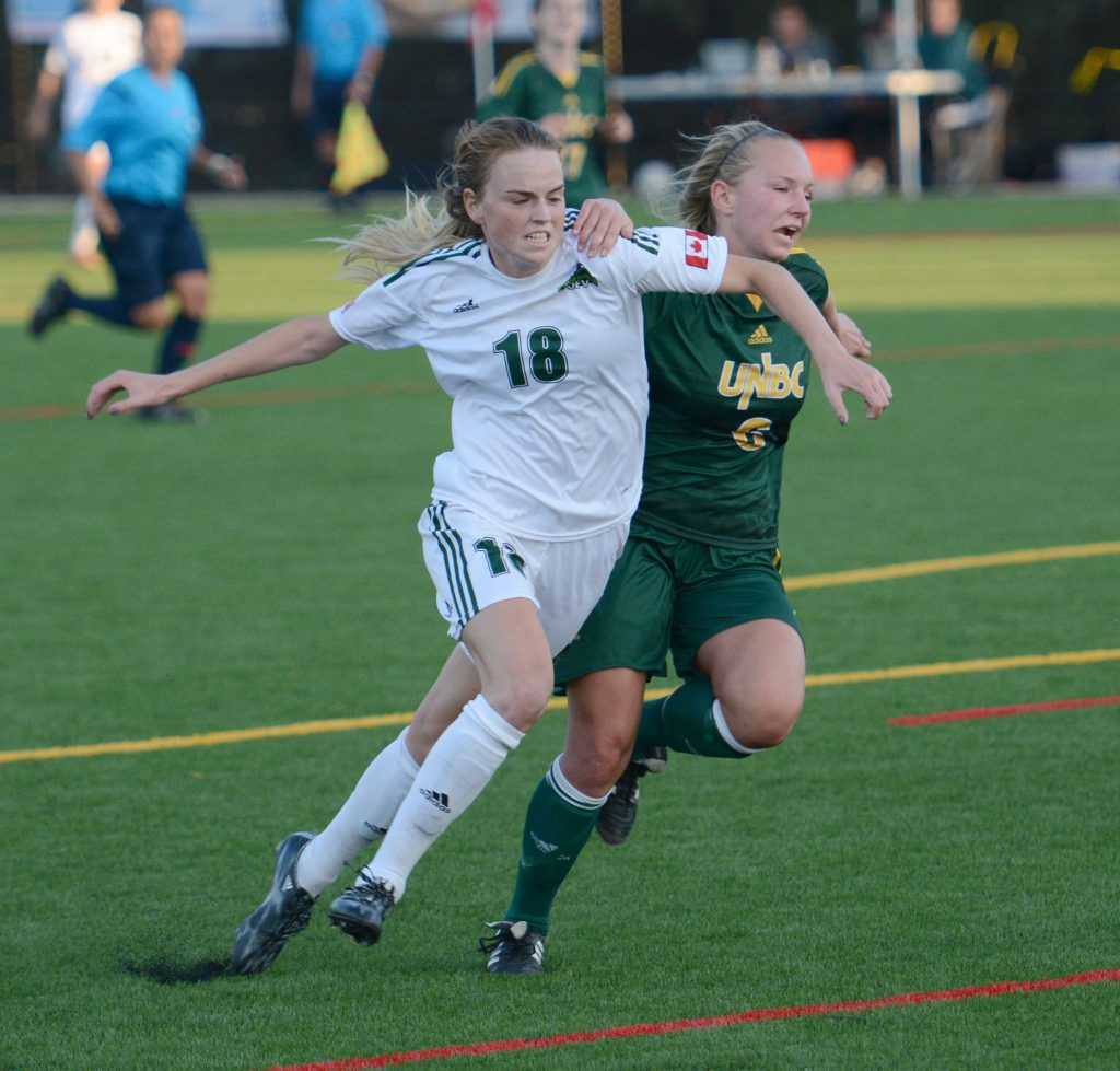 Amanda Carruthers (left) battles for position with a UNBC defender.