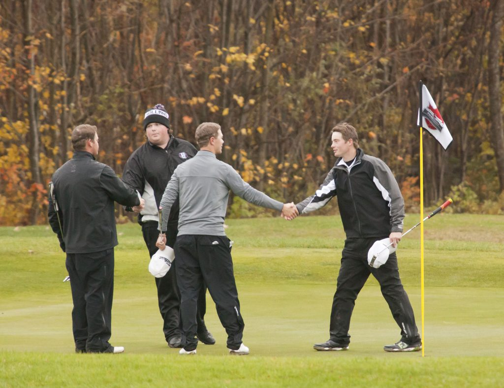 UFV's Zach Olson (left) shakes hands with his opponents following Friday's blustery final round.